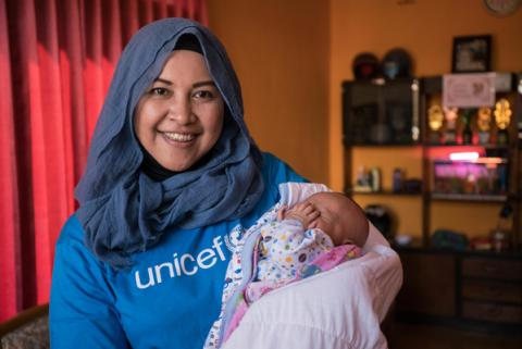UNICEF staff member with newborn baby