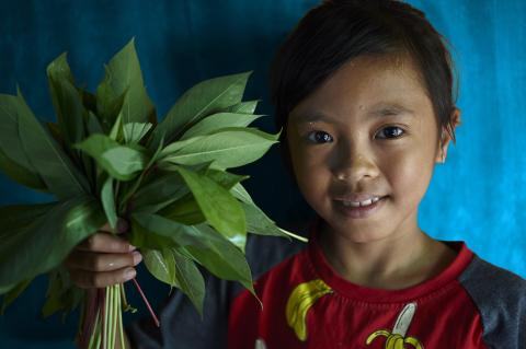 Suci, 10, holds up vegetables that she collected from her family's garden.