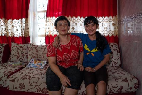 Flora Dita Cahyani and her mother sitting at their home