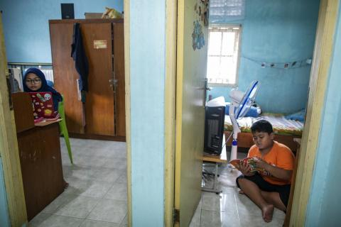Arkan, 9 (right), studies at home while keeping a safe distance from his sister Siwi (left)