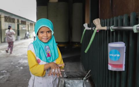 Ais, 7, washes her hands at an orphanage where she lives in Jakarta.