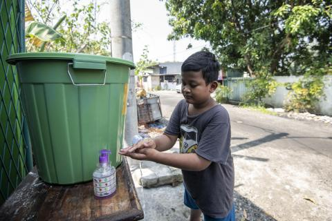 A boy washes his hands at a hand washing station in his village in Bekasi