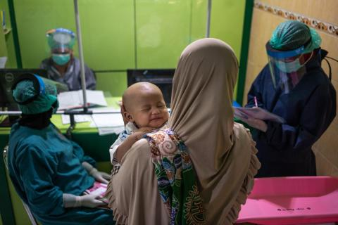 A mother waits for her child to be vaccinated