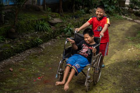 Syaiful, 12, a child with a physical impairment, is pushed in a wheelchair by his best friend Kevin Saputra, 9, a child with a visual impairment, as they play outside near Syaiful's house in Banyumas, Central Java, Indonesia.