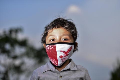 Etno wears a red and white Indonesian flag face mask outside his home