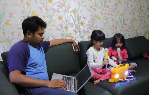 Father works from home while his children are playing