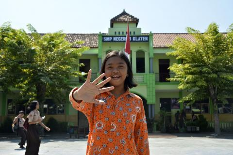 Devi, 15, makes an 'end violence' hand sign outside SMP Negeri 3 (Junior Secondary School)