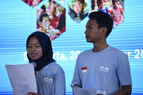 Children read a statement expressing their hopes for the future at an event marking World Children's Day in the city of Surakarta