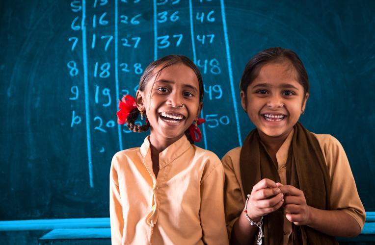 Two girls smiling in the classroom.