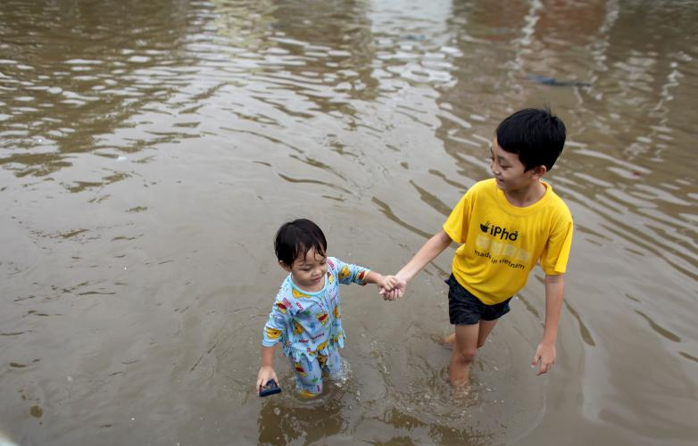 A small girl holds an older boy's hand as they wade across a flooded street