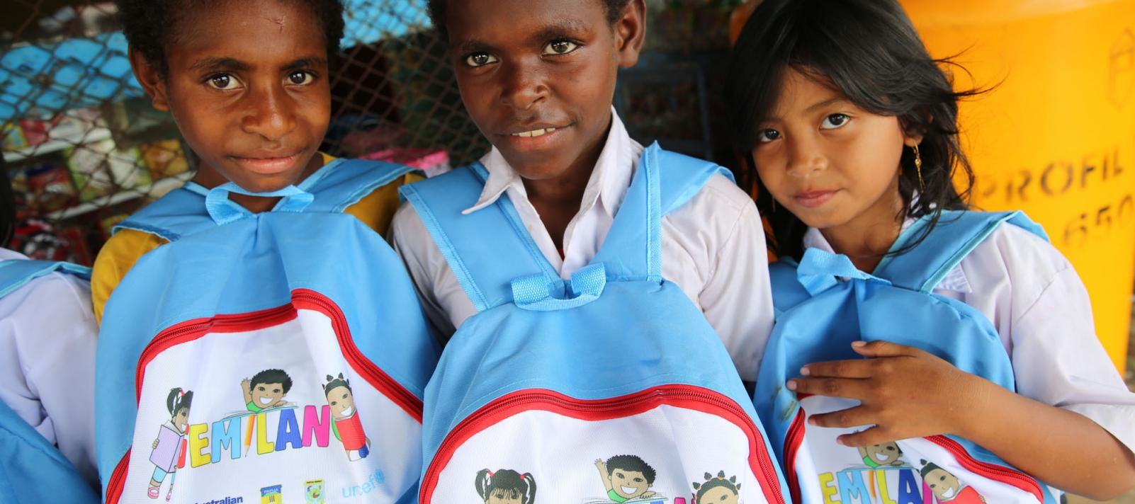 Three children posing with their school bags.