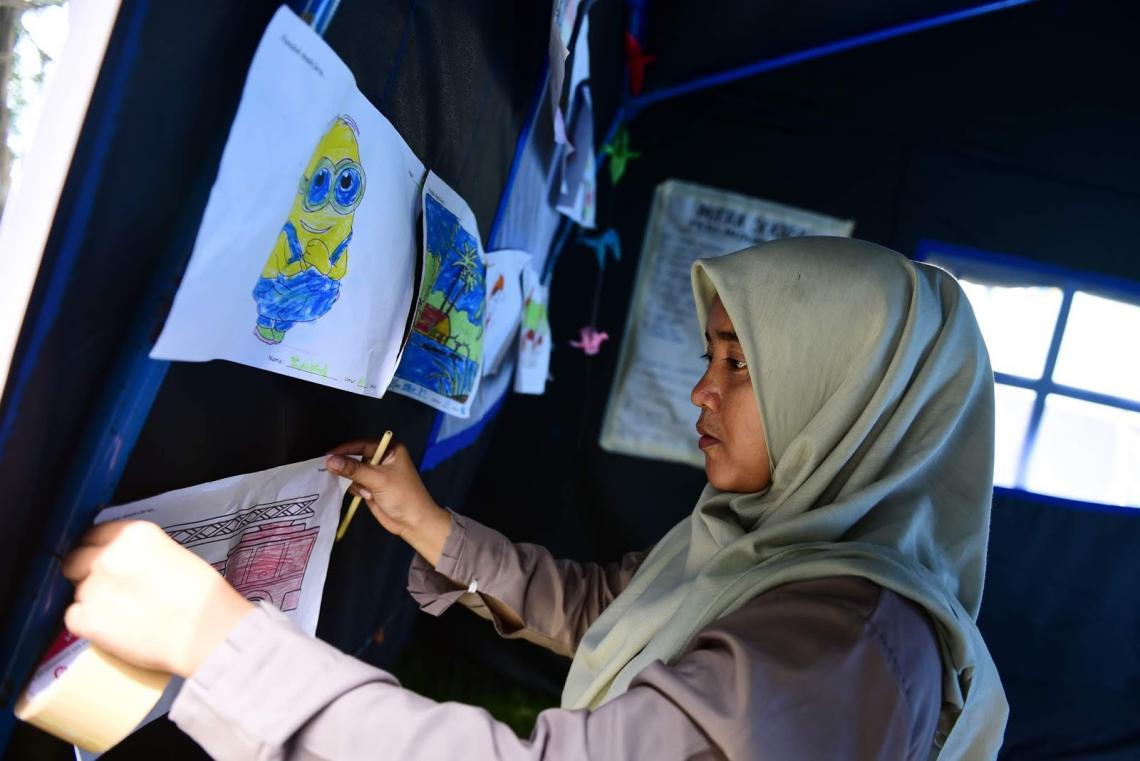 Fadlun Badjerey, a social worker from the Ministry of Social Affairs, puts up drawings made by children who survived the tsunami and earthquake on 28 October.