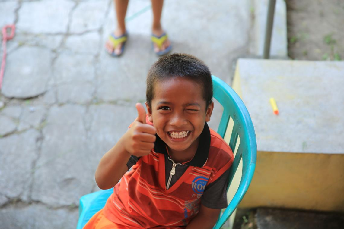 A young boy winking and showing thumbs up.