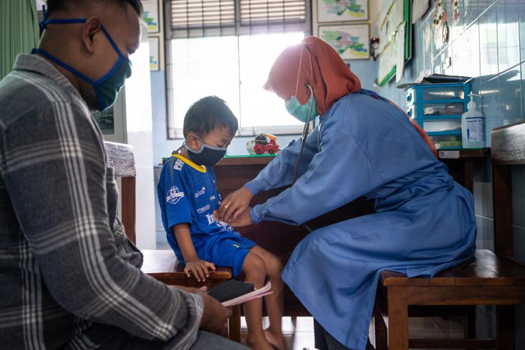 A nurse wears a mask when treating a patient in Puskesmas Bayat, Klaten, Central Java