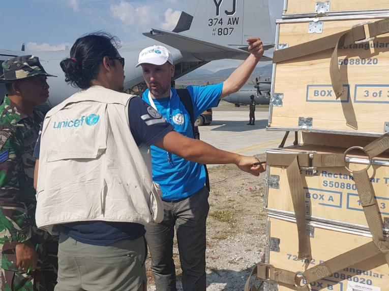 "Ridwand ""Doc Jack"" Gustiana, UNICEF Emergency Health Officer, and Stephane Arnaud, UNICEF Senior Supply Officer, receive the first batch of 33 ""schools in a tent"" in Palu, Central Sulawesi"