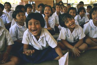 Children in school sitting down smiling, laughing