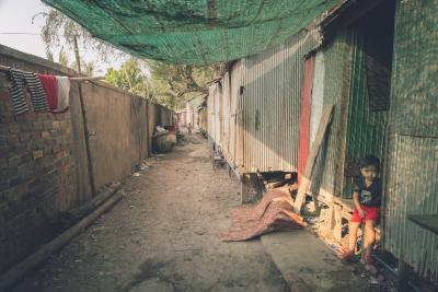 Child sitting down in a street in a slum area