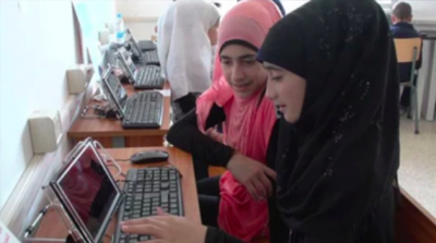 Two young girls working on a laptop