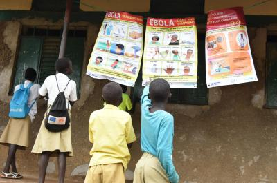 Students at Kinji Primary School are studying the banners with information about Ebola Virus Disease.