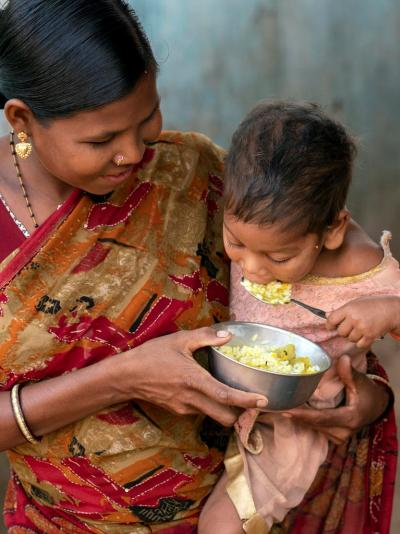 Mother feeds child with the help of a bowl