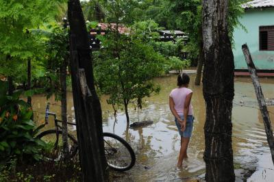 An adolescent girl walks through the flooded yard in front of her home near the Sinú River, in the northern municipality of Cotorra in Córdoba Department. Beside her is a bicycle.