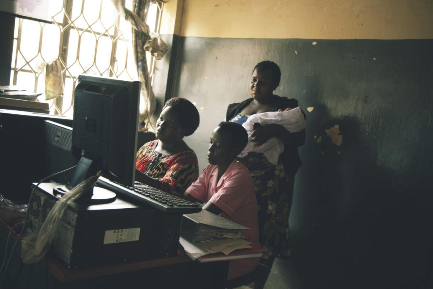 Health workers look at the monitor screens