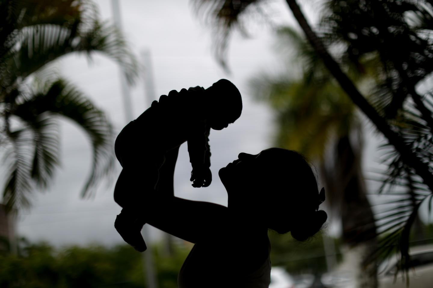 Alice,15 years old, holds her a 4-month old baby born with microcephaly in Recife