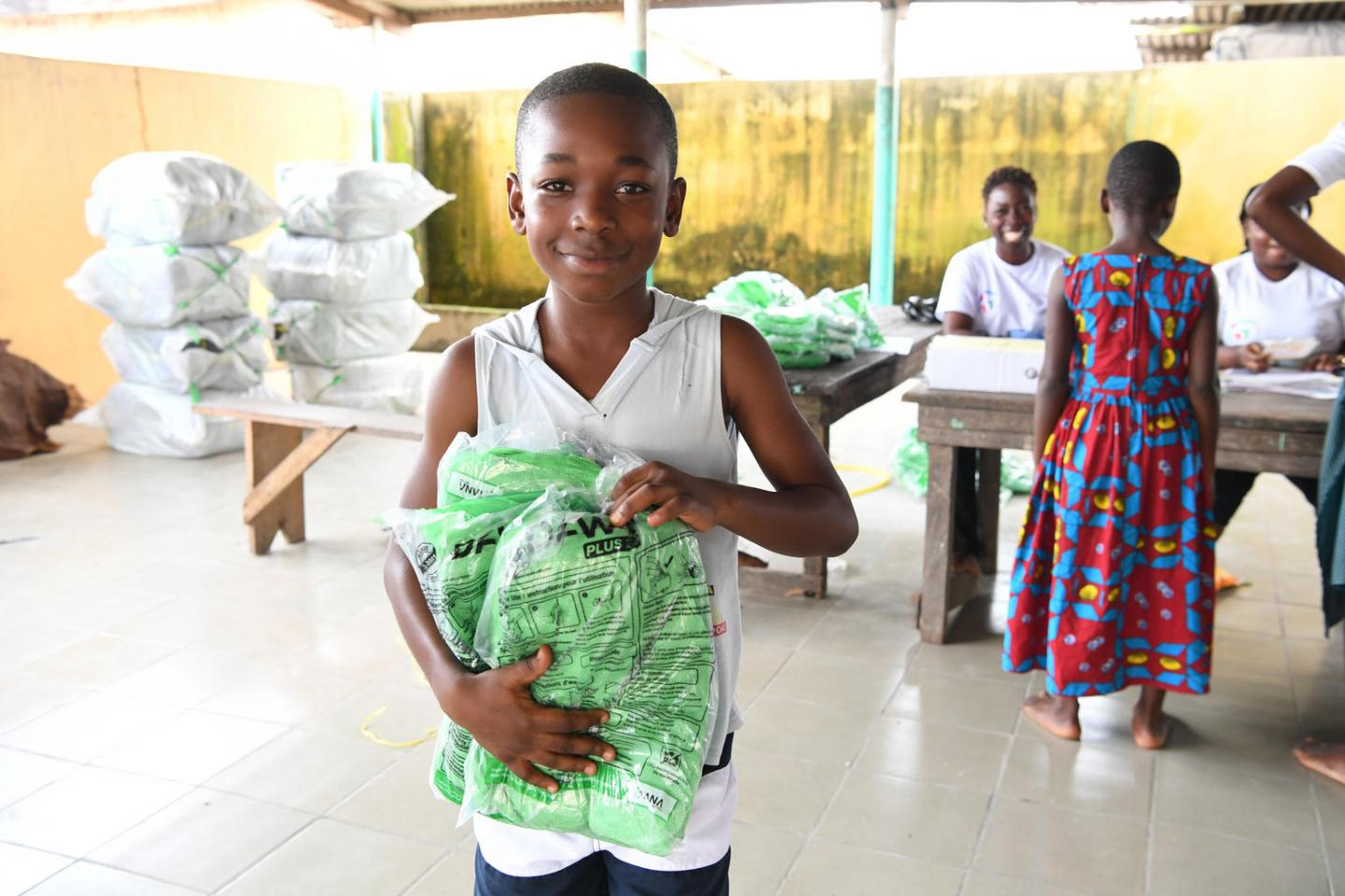 In the village of Sikensi, in the South East of Côte d'Ivoire, a boy receives a insecticide treated mosquito net.