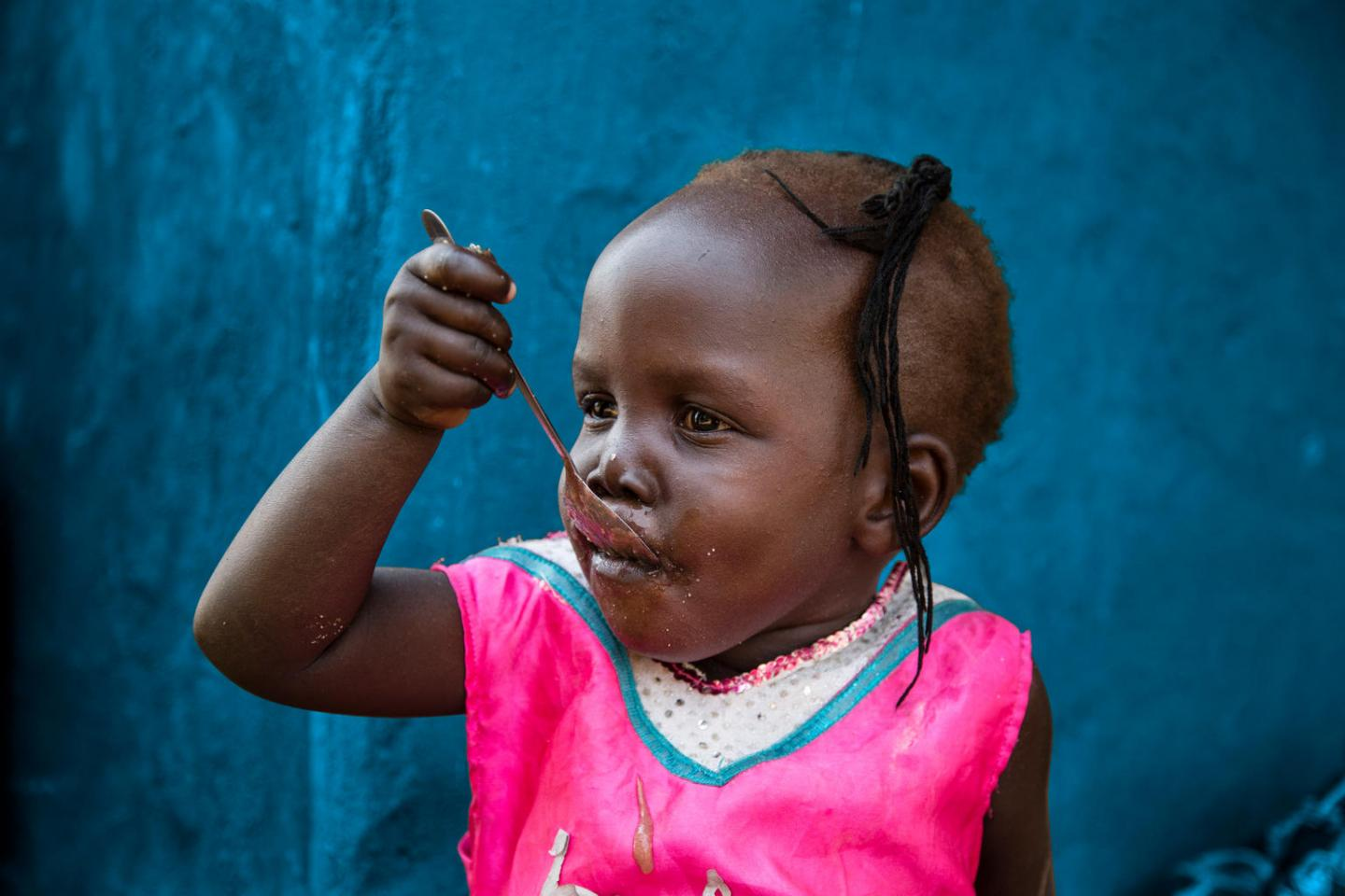 in South Sudan, Grace, 2, eats porridge outside her home