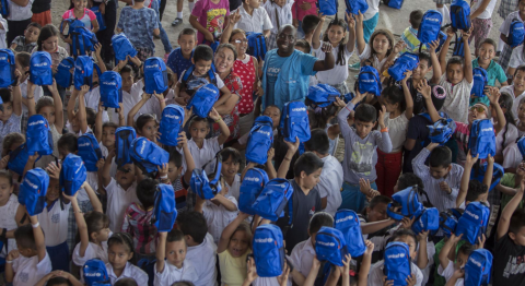 Children looking at the camera holding UNICEF back packs