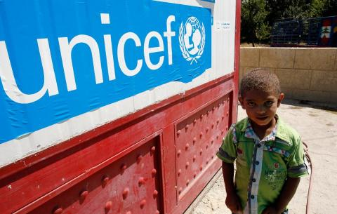 Child in front of UNICEF banner