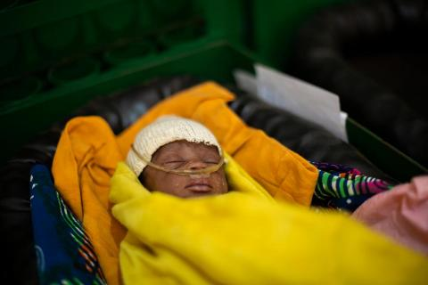 A baby wrapped in a yellow blanket receives oxygen via a nasal cannula