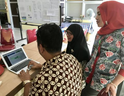 I Made Suwancita, UNICEF RapidPro consultant, looks at the dashboard with Ibu Enung Nurhayati, immunization coordinator, and Ibu Dr Rahmi, head of this health centre.