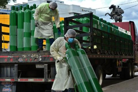 Men wearing PPE unload oxygen cylinders from a truck