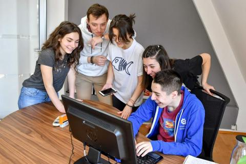 youth team brainstorming and working with a computer