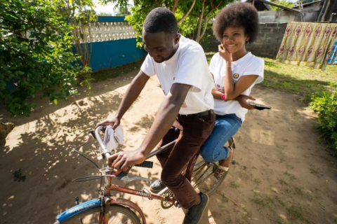 Ragia Ngao Amade, 17, rides on a bike with a friend. She volunteers for four hours a day as a counsellor for SMS Biz/U-Report's counselling service.