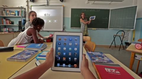 Elementary school children use electronic tablets on the first day of class in the new school year in Nice, September 3, 2013. Eric Gaillard/Reuters