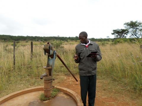 man beside a water pump and checking if it is working