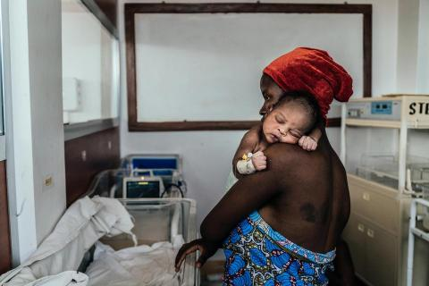 A mother holds her baby in a hospital