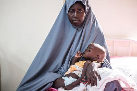 Fatima Masai, whose baby boy Mohamed suffers from severe acute malnutrition, sits with him at a critical care ward of the University of Maiduguri Teaching Hospital, Maiduguri, Borno State, Nigeria