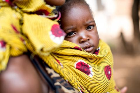 A child is carried by its mother attending a clinic held by a community nurse where basic health care services, including growth monitoring and immunizations, are provided to infants and children in the Chibolele area, Ndola, Copperbelt Province, Zambia