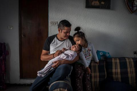 Denis holds his daughter Denisse, 9 months, who was born with congenital Zika syndrome, as Denisse's sister Emma kisses her at the family's home in Guatemala City, Guatemala