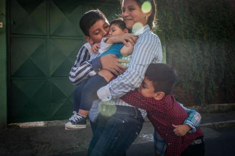 On 18 October 2017 in Guatemala, 9-month-old Danilo (centre), carried by his smiling mother, Sandra, is showered with hugs and kisses from his brothers, (left-right) Denis, 13, Dorian (arm visible), 4, and Dylan, 6, inside their home, in Guatemala City, the capital.