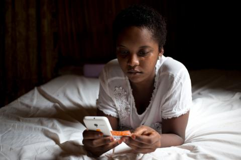 16-year-old Charmela loads credit to her mobile phone, in her home on the island of Nosy Be, off the northwest coast of Madagascar.