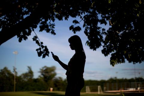 essica Marques, 20, checks her mobile phone underneath a tree in a park in Taiobeiras municipality in the Southeastern state of Minas Gerais, Brazil.