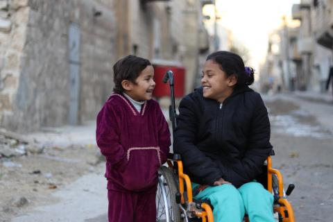 Hanaa, 8, who was paralysed by an exploding bomb and lost the use of her legs, sits in a wheelchair next to her sister Khadija, 5, near their home in Sakhoor neighborhood, east Aleppo city, Syrian Arab Republic.