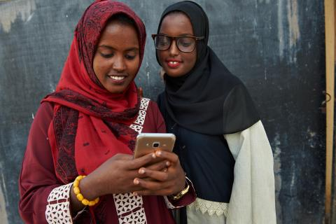 "Adolescent girls look at social media posts while attending a ""Lifeskills"" event in Union Development & Culture Community Centre in Djibouti."