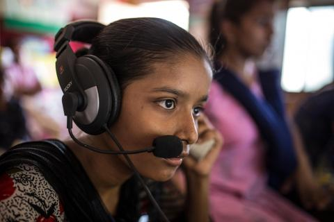 Sandhya Sahu listens audio from computer inside Child Resource Centre at slums of Shivaji Nagar in Mumbai, India.