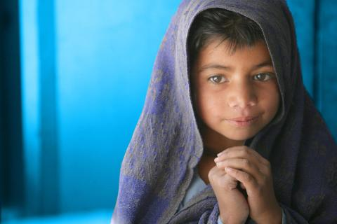 A girl wrapped in a blanket clasps her hands, at Model Primary School for Girls, a 'child-friendly' school in the village of Girani in Balochistan Province.