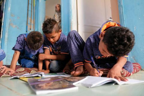 Brothers Mohammad, 5, Osama, 7, and Moneer, 9, write in their exercise books at home where they live with their two sisters, mother and father in Jerash camp, Jordan.